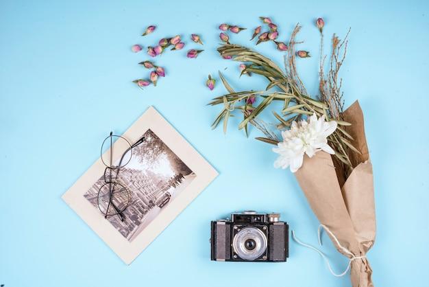 Vue De Dessus Du Vieil Appareil Photo Avec Une Fleur De Chrysanthème De Couleur Blanche Dans Du Papier Kraft Et Des Boutons De Rose Secs éparpillés Sur Bleu Photo gratuit