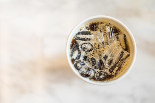 Vue de dessus de emporter un morceau de café noir glacé (americano) sur une table avec espace de copie. Photo Premium