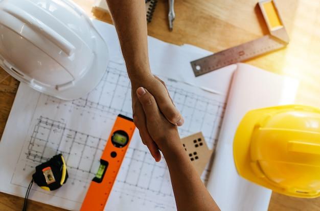 Vue de dessus entrepreneur de l'équipe de travailleur de la construction serrer la main après avoir terminé la réunion d'affaires Photo Premium