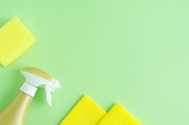 Vue De Dessus Des éponges De Lavage Jaunes Et Vaporisateur Pour Le Nettoyage Sur Vert Photo Premium