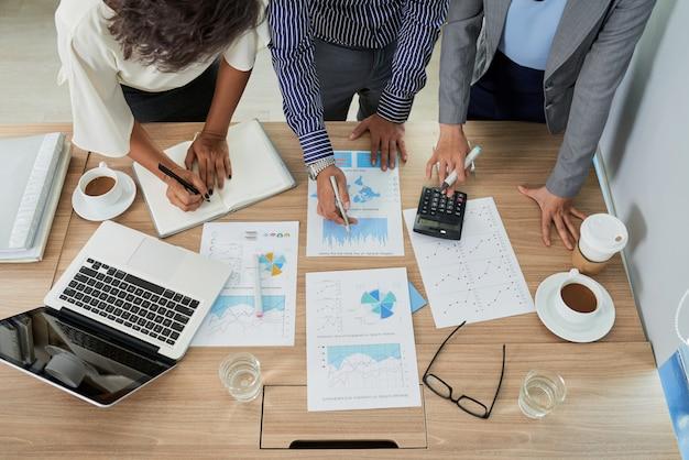 Vue de dessus d'une équipe de personnes travaillant avec des documents calculant les gains Photo gratuit