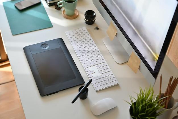 Vue de dessus, espace de travail d'artiste designer, ordinateur, tablette de dessin numérique et fournitures créatives Photo Premium