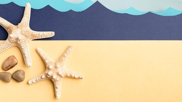Vue De Dessus Des étoiles De Mer Et Des Rochers Avec Papier Océan Photo gratuit