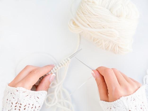 Vue de dessus d'une femme faisant du crochet avec de la laine blanche Photo gratuit