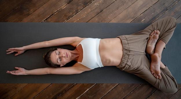 Vue De Dessus De La Femme à La Maison Pratiquant Le Yoga Photo gratuit