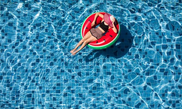 Vue de dessus de la femme s'étendent sur le ballon au fond de la piscine Photo Premium