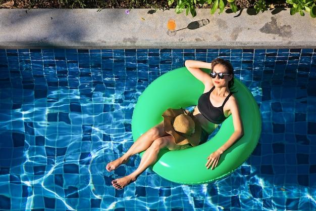 Vue de dessus de la femme s'étendent sur le ballon dans la piscine Photo Premium