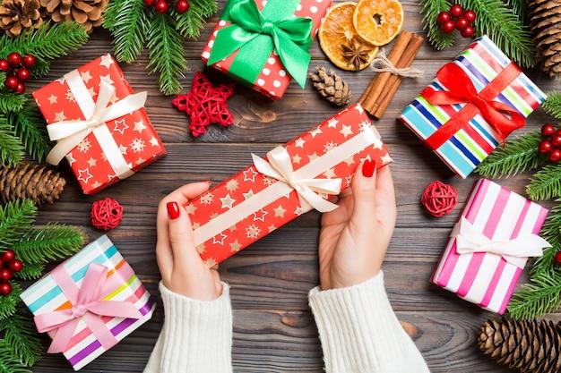 Vue de dessus une femme tenant une boîte-cadeau dans ses mains sur une fête en bois. sapin et décorations de noël. temps Photo Premium