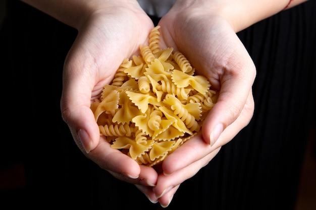 Une Vue De Dessus Femme Tenant Des Pâtes Alimentaires Crues Et Jaunes Pâtes Italiennes Photo gratuit