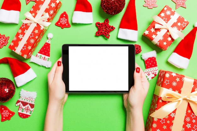 Vue De Dessus De La Femme Tenant La Tablette Dans Ses Mains Sur Le Vert Fait De Décorations De Noël. Photo Premium
