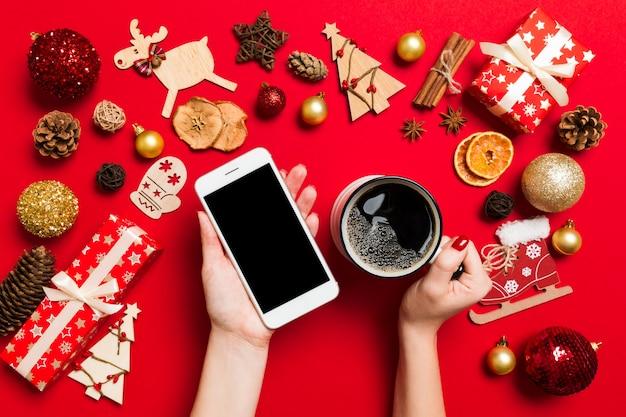 Vue de dessus d'une femme tenant un téléphone dans une main et une tasse de café dans une autre main sur le rouge Photo Premium