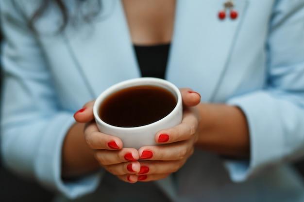 Vue de dessus femme en veste bleue tenir une tasse de café Photo Premium
