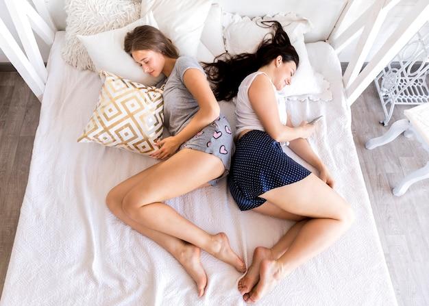 Vue de dessus des femmes dormant dos à dos Photo gratuit