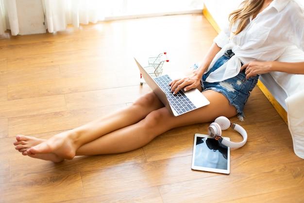 Vue de dessus des femmes utilisent un ordinateur portable pour faire du shopping en ligne à domicile Photo Premium