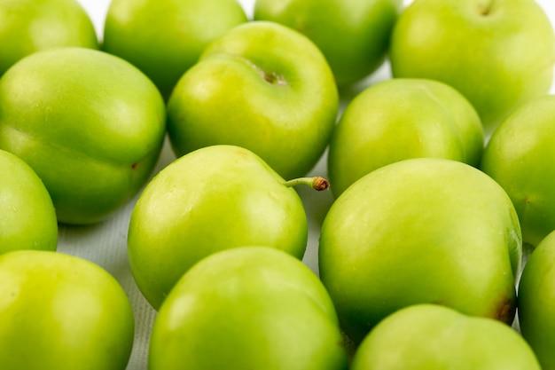 Une Vue De Dessus Fermée De Cerise-prune Verte Ronde Isolé Aigre-doux Frais Sur Le Fond Blanc De La Qualité Des Fruits Photo gratuit