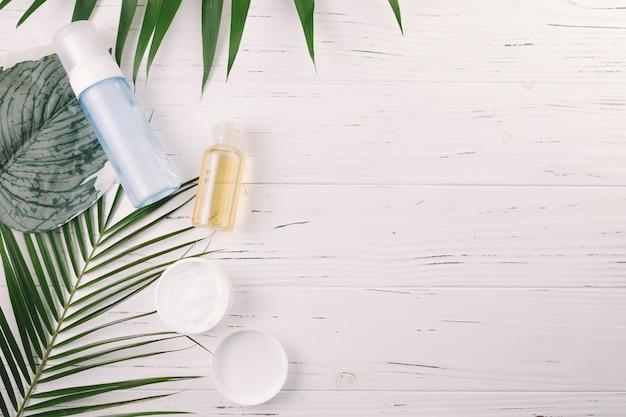 Vue de dessus des feuilles tropicales avec des outils de beauté et des produits de beauté Photo gratuit