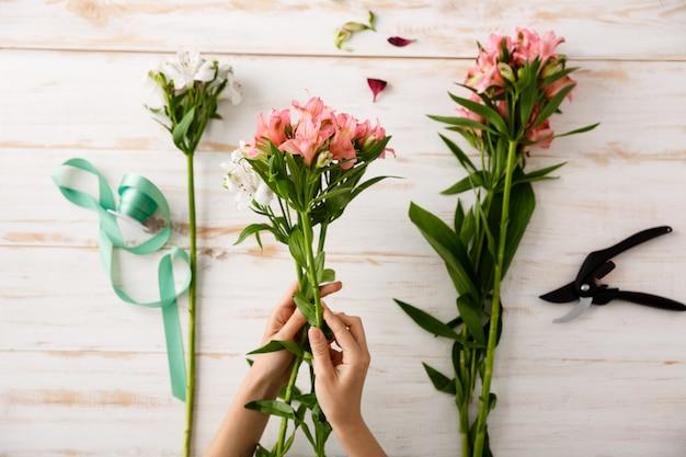 Vue De Dessus Fleuriste Mains Faisant Bouquet De Fleurs Photo gratuit