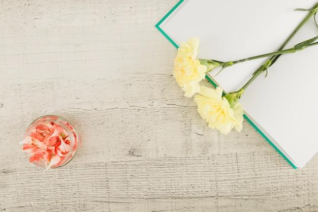 Vue de dessus des fleurs et livre sur fond en bois Photo gratuit