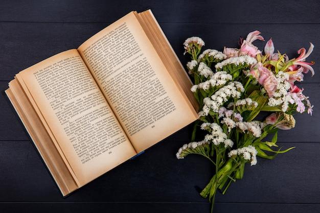 Vue De Dessus Des Fleurs Rose Clair Avec Un Livre Ouvert Sur Une Surface Noire Photo gratuit