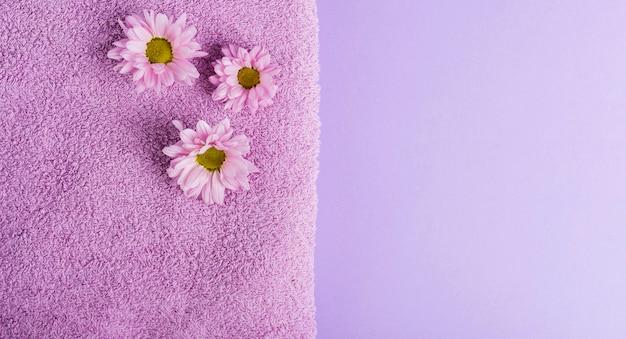 Vue de dessus fleurs violettes et serviette avec espace de copie Photo gratuit