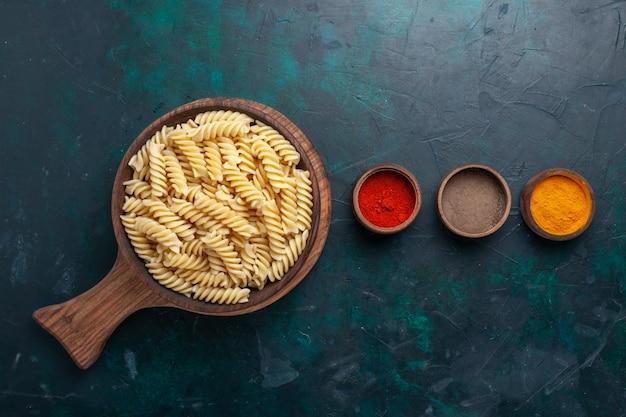 Vue De Dessus En Forme De Pâtes Italiennes Avec Assaisonnements Sur Le Bureau Bleu Foncé Photo gratuit