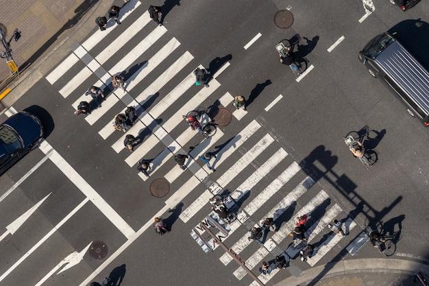 Vue De Dessus De La Foule Des Piétons Personnes Indéfinies Marchant Surpasser L'intersection De La Rue Traverser Avec Le Soleil Photo Premium