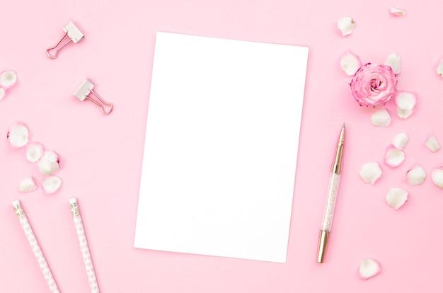 Vue De Dessus Des Fournitures De Bureau Rose Avec Des Pétales De Rose Photo gratuit