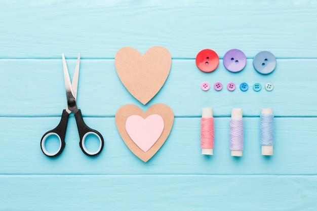 Vue de dessus des fournitures de couture avec des coeurs en papier de la saint-valentin Photo gratuit