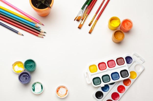 Vue de dessus de fournitures de peinture aquarelle, pinceaux et crayon coloré. processus de création de peinture à l'aquarelle. espace de copie. Photo Premium