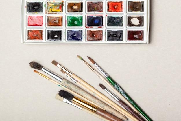 Vue de dessus de fournitures de peinture aquarelle, pinceaux et crayon coloré. Photo Premium