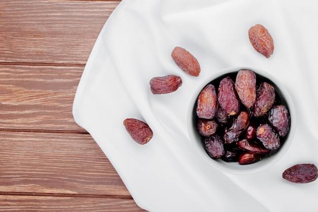 Vue De Dessus Des Fruits De Datte Séchés Sucrés Dans Un Bol Sur Une Nappe Blanche Sur Fond De Bois Avec Copie Espace Photo gratuit