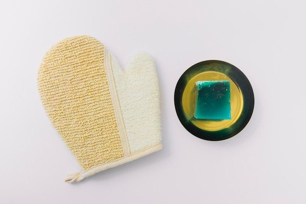 Vue de dessus de gant de loofah et barre de savon vert sur plaque isolé sur fond blanc Photo gratuit
