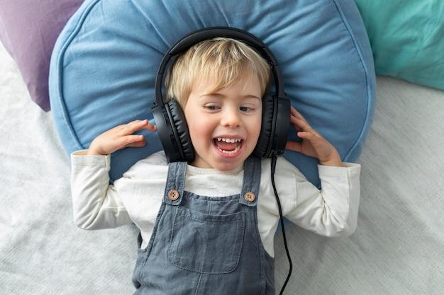 Vue De Dessus Garçon écoutant De La Musique Sur Des écouteurs Photo Premium