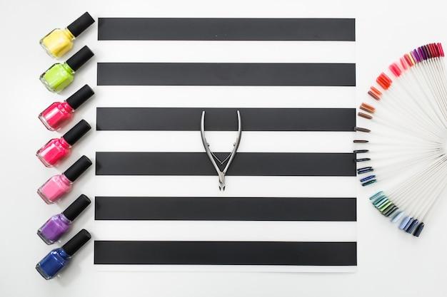 Vue de dessus gros plan image de poussoir de cuticules et palette de couleurs de vernis à ongles sur la table Photo Premium