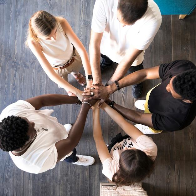 Vue de dessus groupe d'amis tenant par la main Photo gratuit