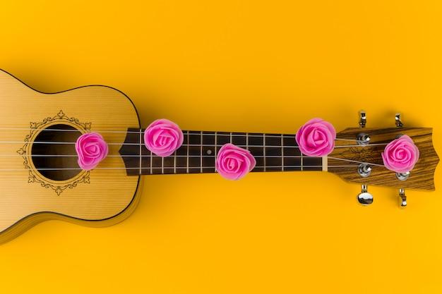 Vue de dessus d'une guitare avec des fleurs roses sur les cordes se trouve sur jaune vif Photo Premium