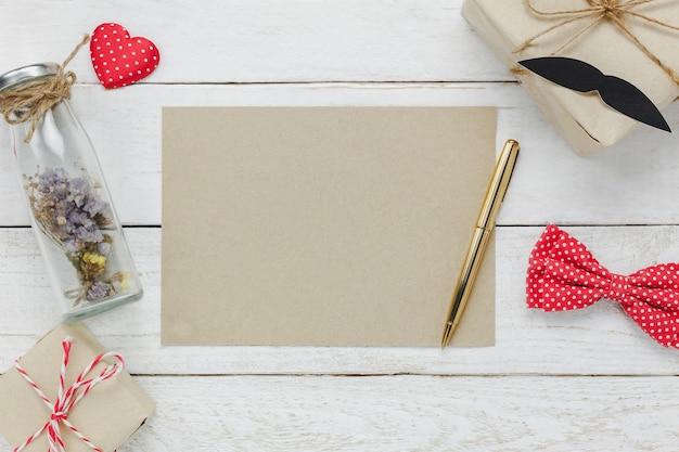 Vue de dessus happy father day.blank space paper pour texte gratuit sur fond de bois rustique.accessoires avec coeur rouge, cadeau, moustache, cravate vintage, fleurs séchées dans la bouteille et le cadeau. Photo gratuit
