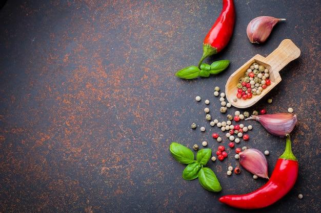Vue de dessus des herbes aux épices. poivron rouge, ail, feuilles de basilic, grains de poivre sur fond de béton foncé Photo Premium