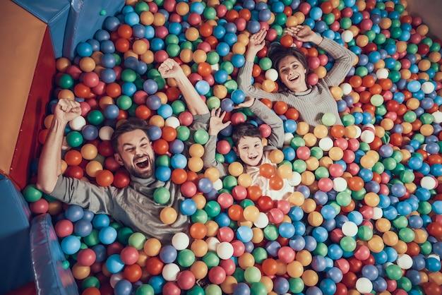 Vue De Dessus. Heureuse Famille Se Trouvant Dans La Piscine Avec Des Balles Photo Premium