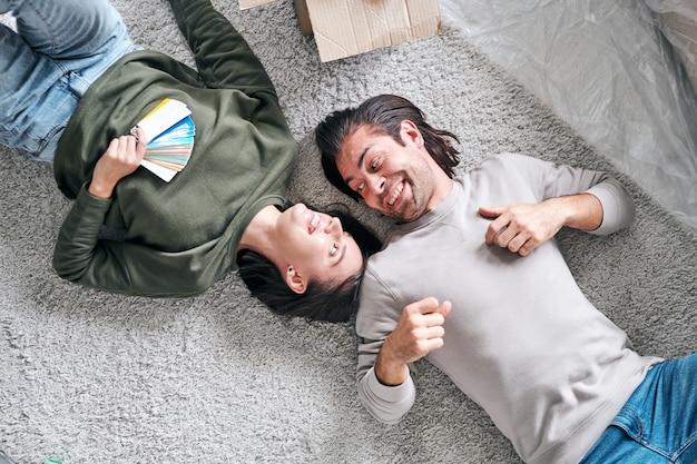 Vue De Dessus De L'heureux Jeune Couple Amoureux Allongé Sur Le Sol Dans Leur Nouvelle Maison Ou Appartement Après Avoir Enlevé Et Discuté Des Idées Photo Premium