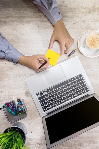 Vue de dessus d'homme d'affaires écrivant dans des notes autocollantes avec ordinateur portable, café, plante en pot et accessoires Photo Premium