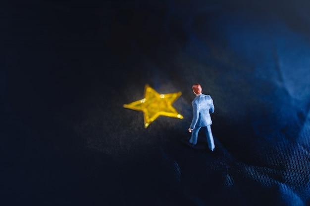 Vue De Dessus D'un Homme D'affaires Miniature, Debout Sur Une étoile Dorée Jaune Photo Premium