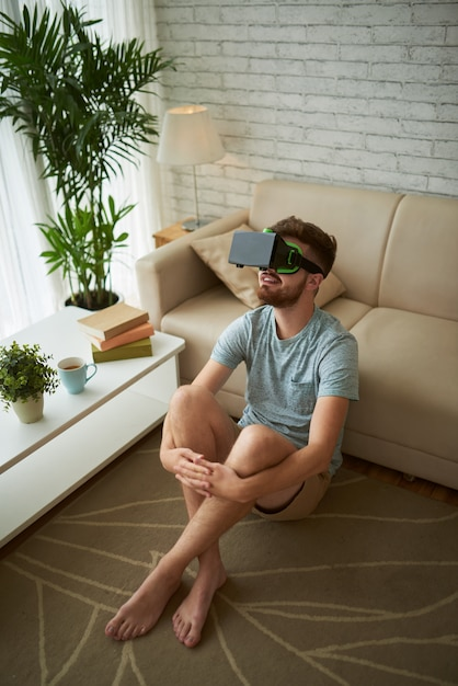 Vue de dessus d'un homme assis sur le sol de son salon en profitant d'un jeu de réalité virtuelle Photo gratuit