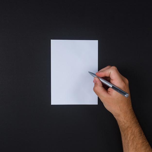 Vue De Dessus L'homme écrit Sur Papier Avec Un Stylo Sur Fond Noir. Photo gratuit