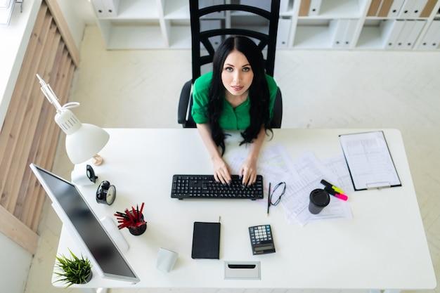 Vue De Dessus D'une Jeune Fille Assise à Un Bureau Et En Tapant Sur Un Clavier. Photo Premium