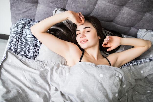 Vue De Dessus De La Jolie Jeune Femme Dormant Bien Dans Son Lit, étreignant Un Oreiller Blanc Doux. Adolescente Au Repos, Bonne Nuit De Sommeil Concept. Photo gratuit