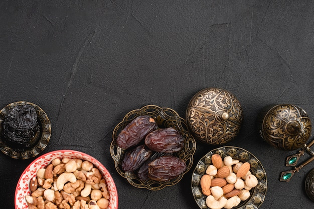 Une vue de dessus de juteuses dates délicieuses et les noix dans un bol métallique sur fond de béton Photo gratuit