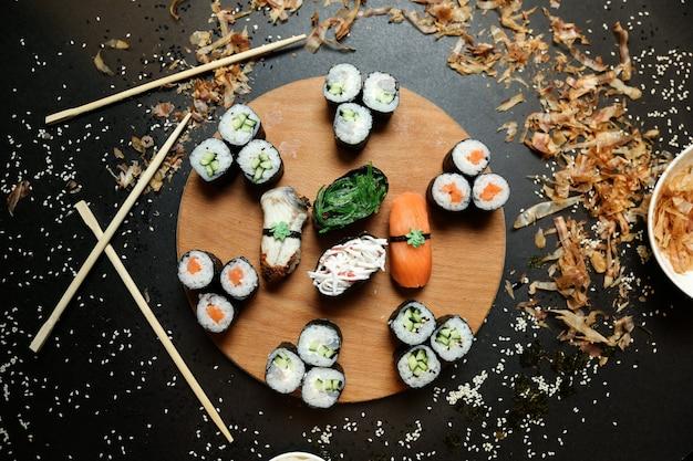Vue De Dessus Kappa Maki Roule Avec Shake Maki Et Sashimi Sushi Avec Des Baguettes Sur Un Support Photo gratuit