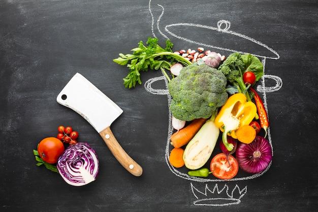 Vue de dessus des légumes colorés sur le pot de craie Photo gratuit