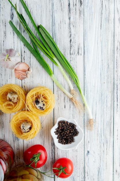 Vue De Dessus Des Légumes Comme œuf De Tomate à L'ail échalote Avec Du Poivre Noir Et Des Vermicelles Sur Fond De Bois Avec Copie Espace Photo gratuit